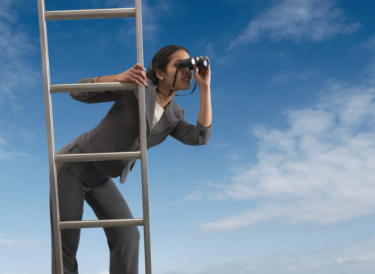 Businesswoman standing on a ladder looking through binoculars --- Image by © Royalty-Free/Corbis